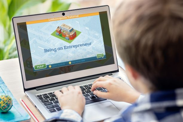 Boy learning about becoming an entrepreneur on laptop